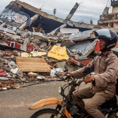 Un hombre conduce su motocicleta junto a casas derrumbadas tras un terremoto en Indonesia