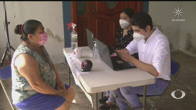 jovenes ayudan a adultos mayores en su registro para ser vacunados contra covid