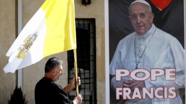 Un hombre en Irak sostiene una bandera del Vaticano (AP)