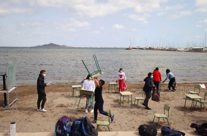 Niños toman clases presenciales en la playa en España
