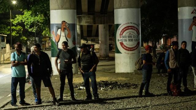 Decenas de migrantes esperan para subirse al tren en la estación de Ferrosur.