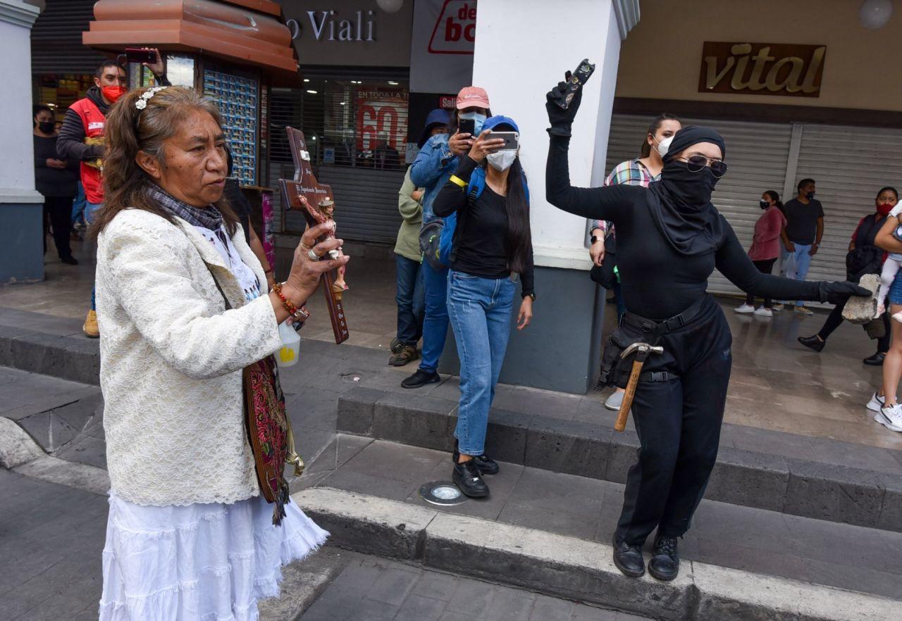 Mujer con cruz arrojó agua bendita a feministas en Toluca
