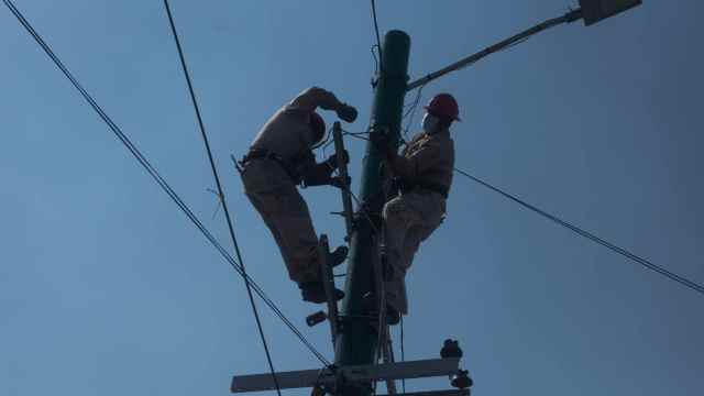 Trabajadores de la Comisión Federal de Electricidad (CFE) arreglan el servicio de luz.