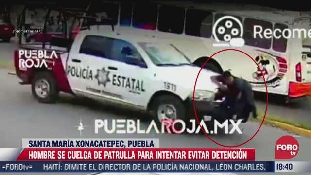 sujeto se cuelga de patrulla para evitar detencion en puebla