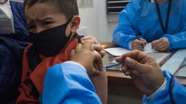 Fotografía que muestra a un niño que es vacunado por una enfermera