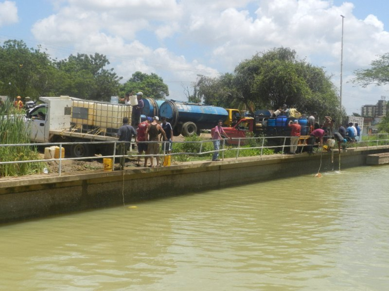 Camionetas y camiones esperan el turno de llenado en la planta de tratamiento..
