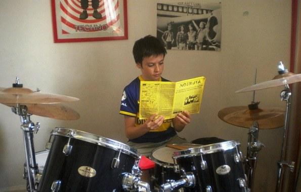 Felix, con su batería y su camiseta bostera, leyendo NOTIRUYA