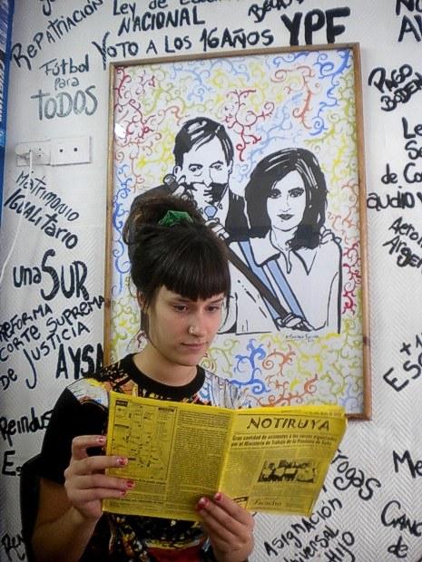 Florencia, militante de La Cámpora, lee NOTIRUYA en La Gloriosa, un centro cultural en Lanús (Buenos Aires). El cuadro que está detrás de ella es de su autoría