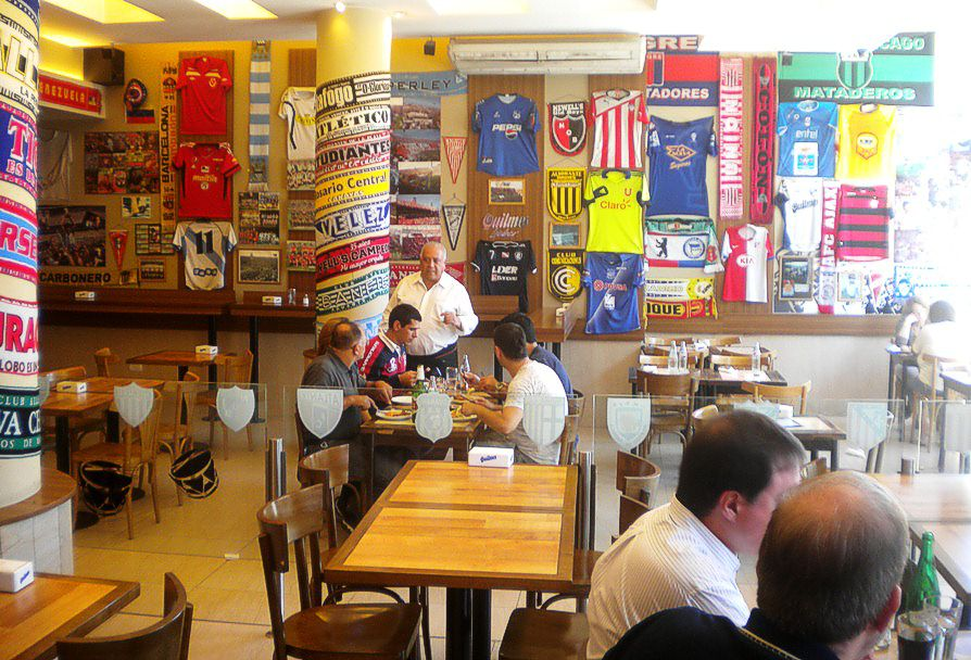 Dentro de una pizzería, decorada al estilo futbolero