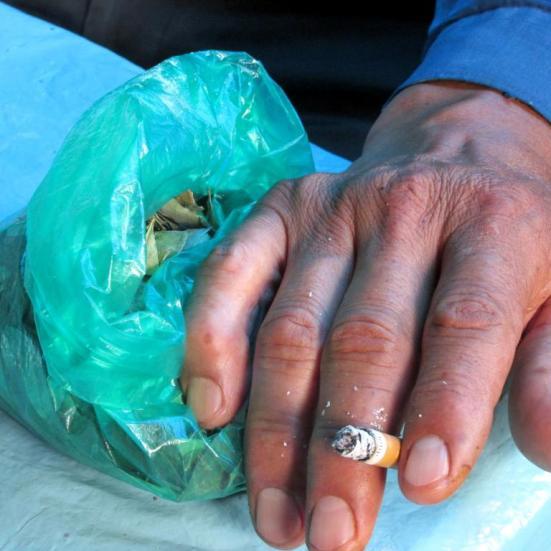 Bolsa con hojas de coca, cigarrillo en mano. Carnaval.
