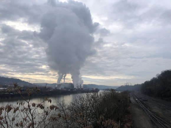 A factory emitting plumes of smoke up into the clouds