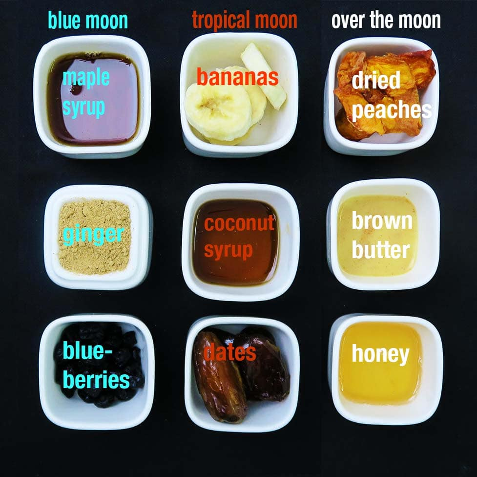 Top down view of assorted containers showing the 3 different flavour variations for Moon Milk Farina. Combination 1 is Blue Moon, featuring maple syrup, ginger, and dried blueberries. Combination 2, called Tropical Moon, is bananas, coconut syrup, and dates. Combination 3 is called Over the Moon and it contains dried peaches, brown butter, and honey.