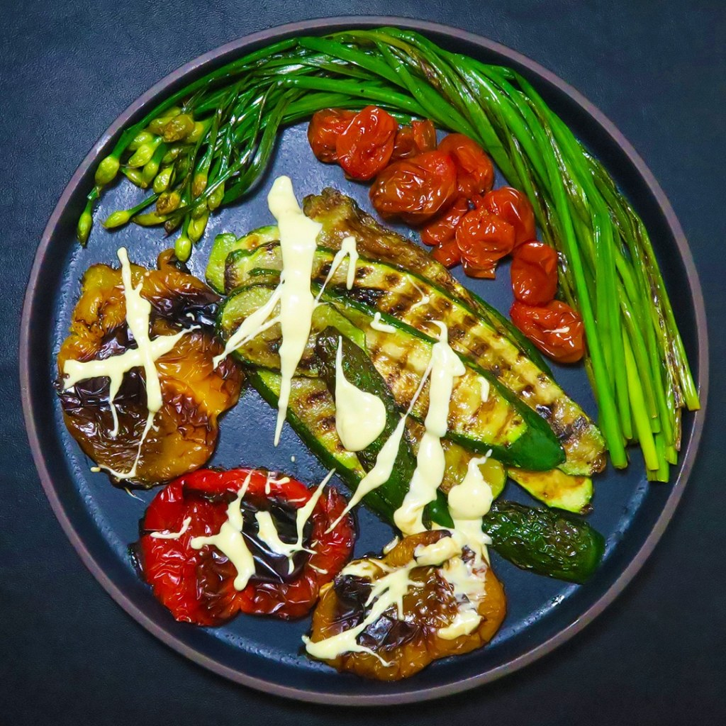 Top-down view of roasted peppers, grilled zucchini, roasted tomatoes, and grilled green onions on a black plate, all topped with 4 minute cheeze sauce, a vegan cheeze sauce.