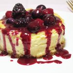 Baked lemon cheesecake, topped with triple berry fruit sauce made from raspberries, blueberries, and blackberries