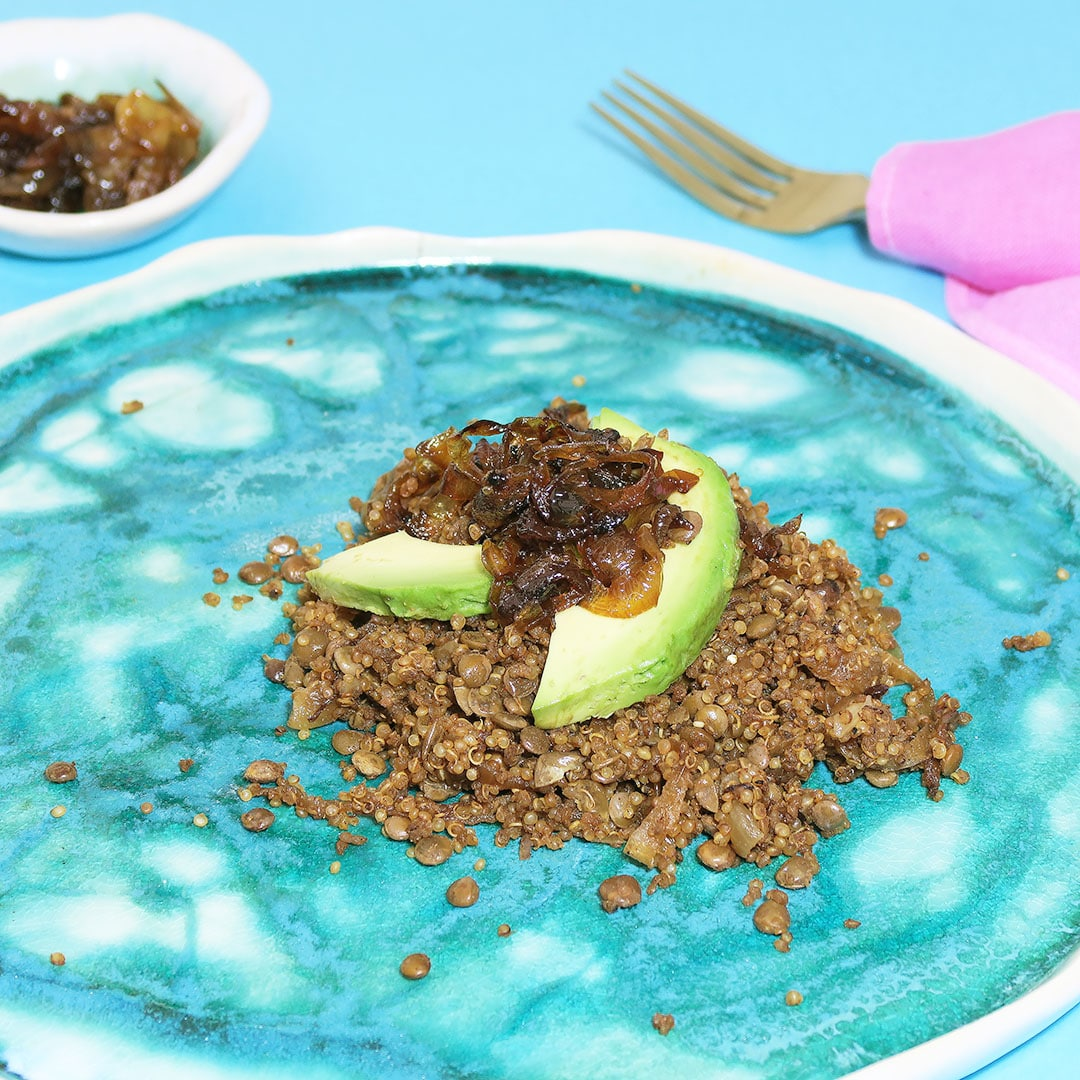 Top down view of Quinoa Mujadara, topped with caramelized onions and avocado, on a blue plate