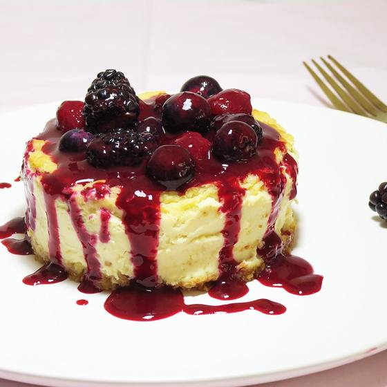 Baked lemon cheesecake topped with cherries, blackberries and blueberries. All on a white plate with a gold fork in the background.