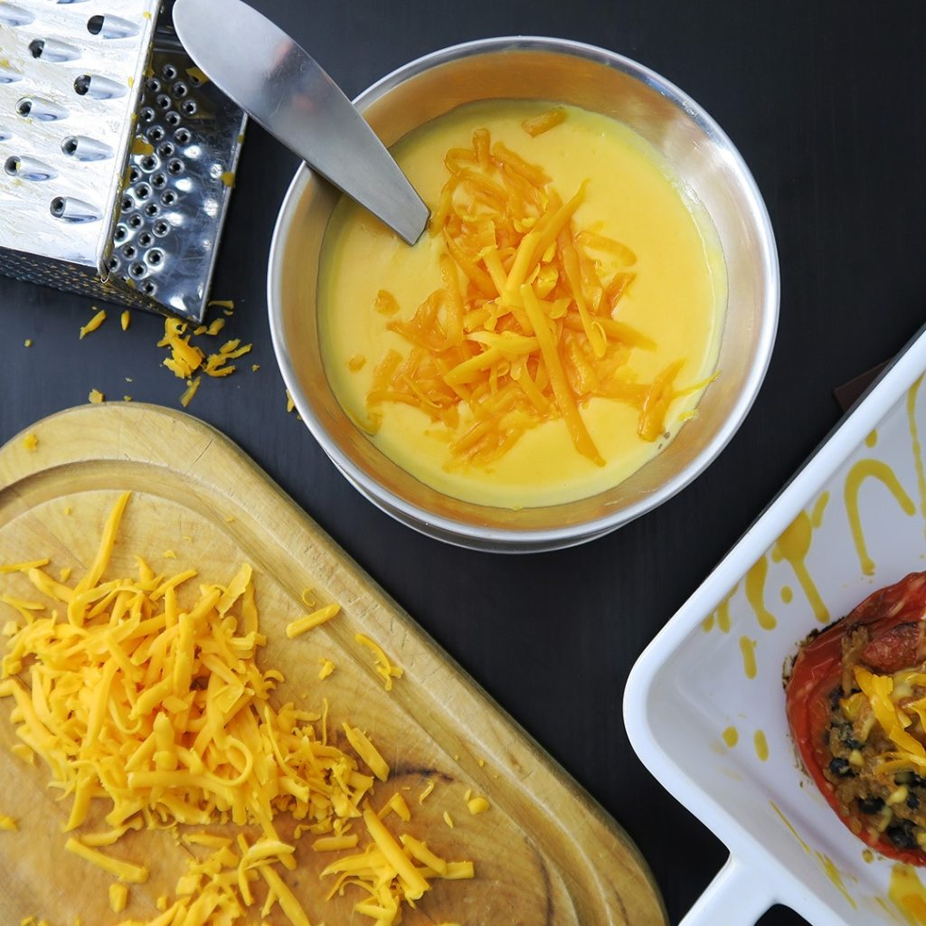 Topdown view of Simple Cheese Sauce in metal dish, with grater and pile of grated cheese on a cutting board.
