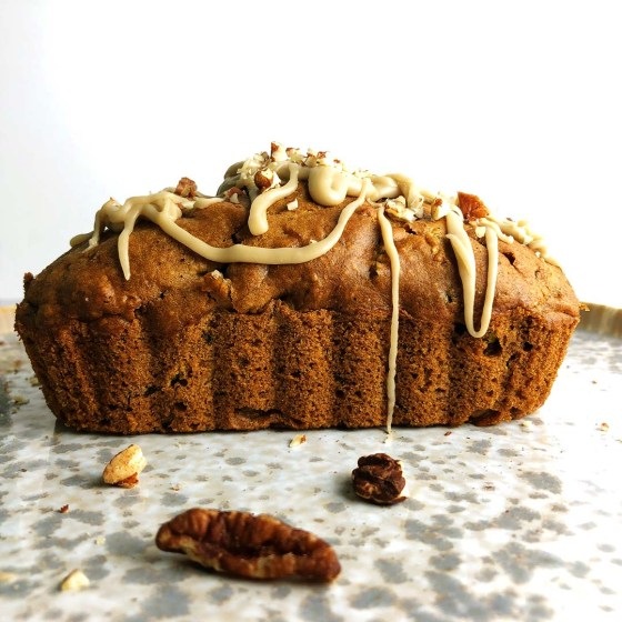 Pear and Zucchini Bread with Vanilla Pecan Drizzle on mottled gray plate against white background