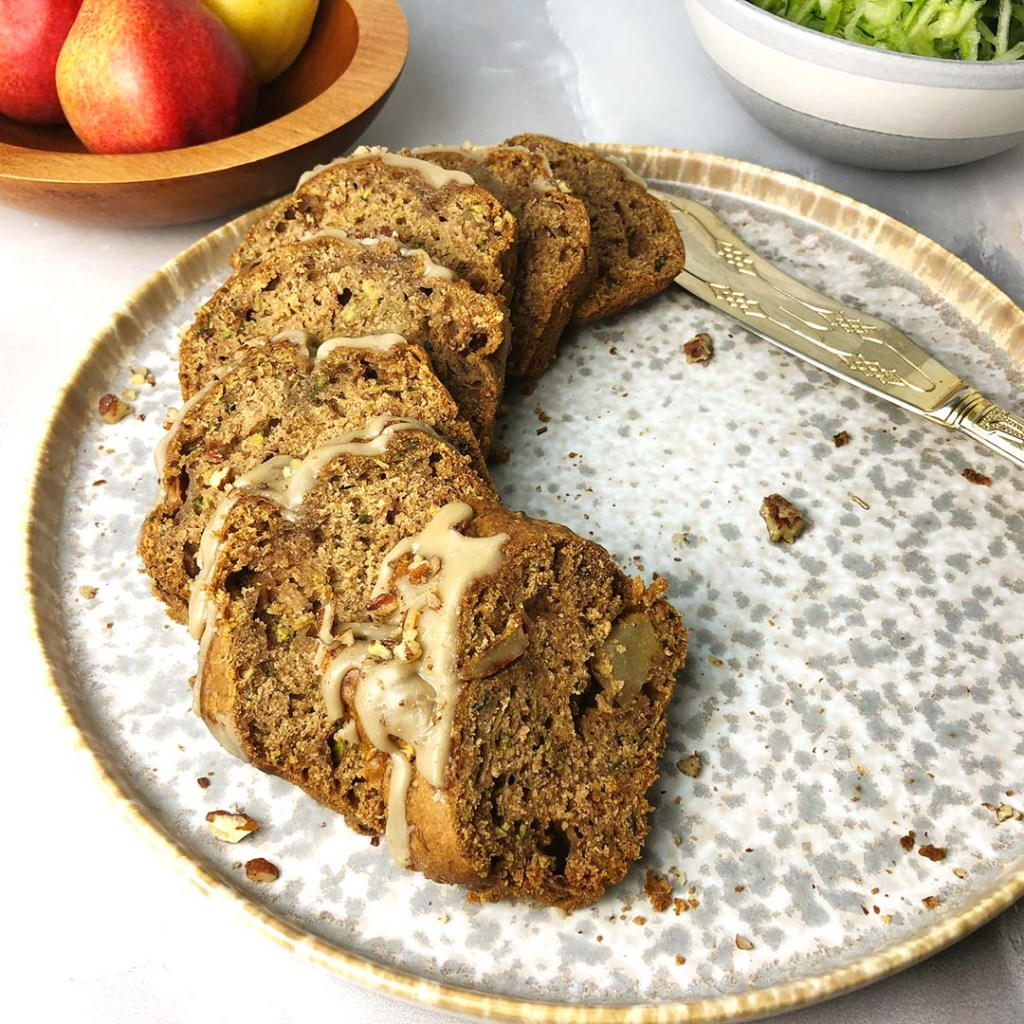 Slices of Pear Zucchini Bread with Vanilla Pecan Glaze on a mottled gray plate, with a bowl of pears and a bowl of shredded zucchinni in the background