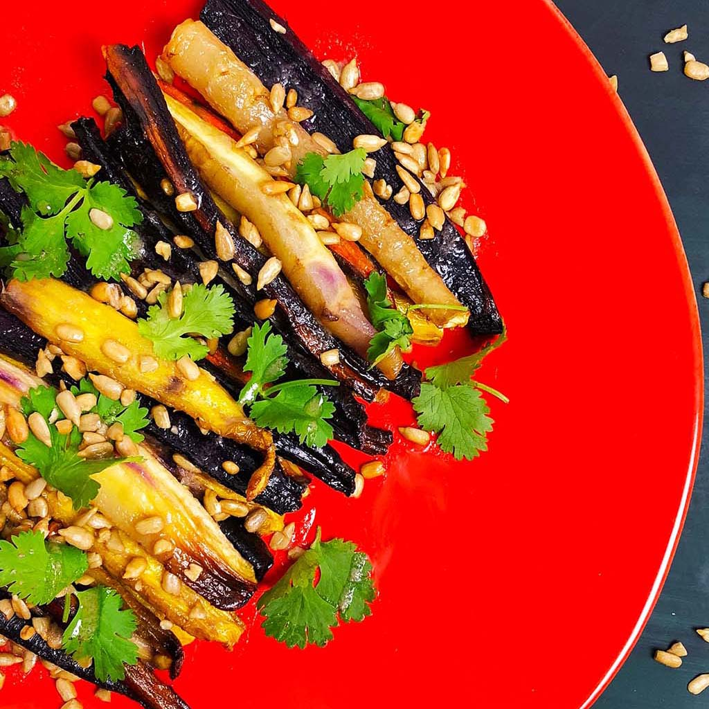 Roasted rainbow carrots, sprinkled with sunflower seeds and cilantro, on a red plate.