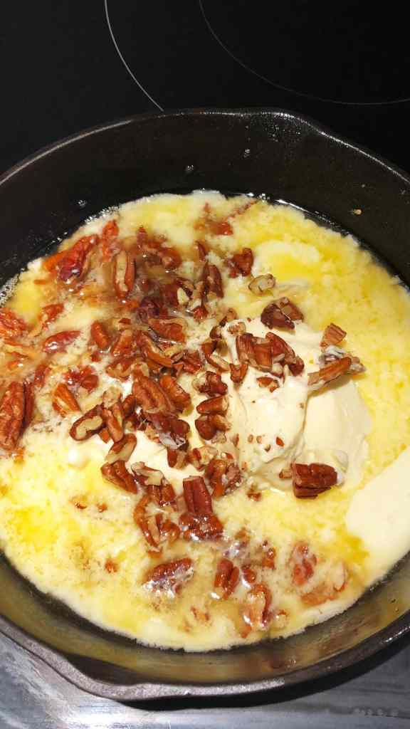 Melted margarine and pecans in a cast iron pan, making vegan brown butter