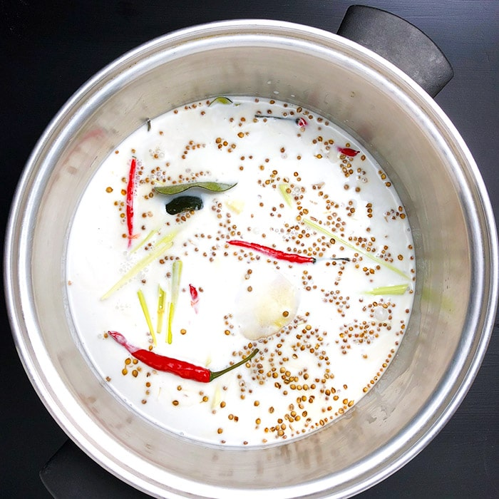 Coconut milk and emongrass, ginger, coriander, lime, and Thai chilies in a large saucepan