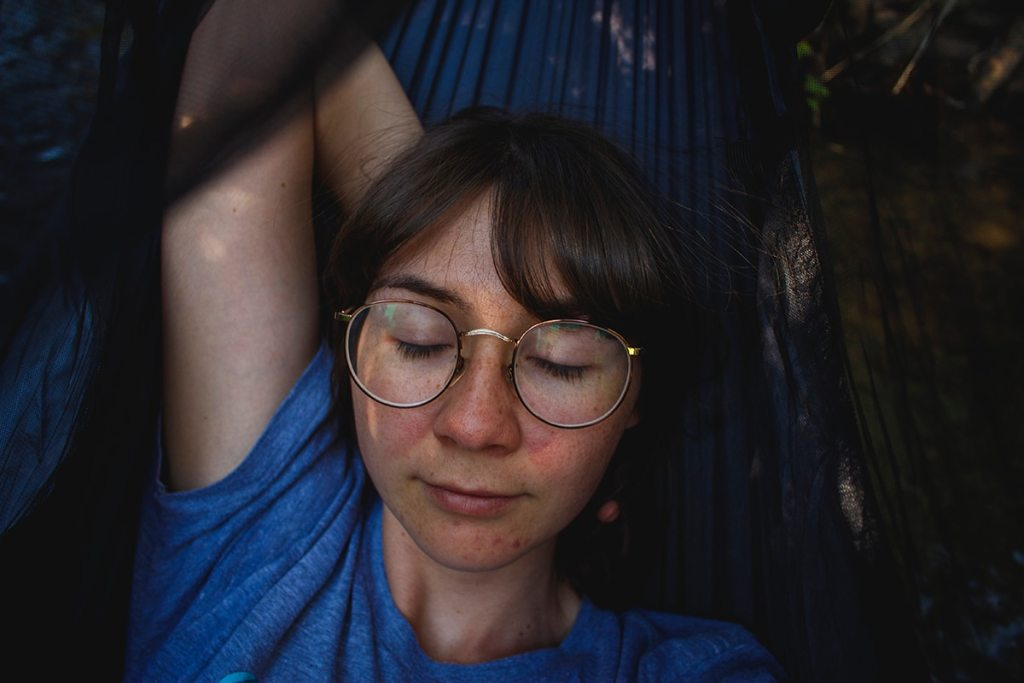 Dark-haired young woman wearing large glasses, lying down in a hammock with eyes closed.