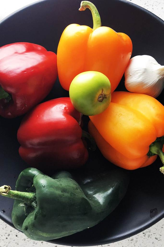 Red, green, and orange peppers in a black bowl. Use different coloured peppers to keep track of which version of Chipotle Cheese Stuffed Peppers you are making.