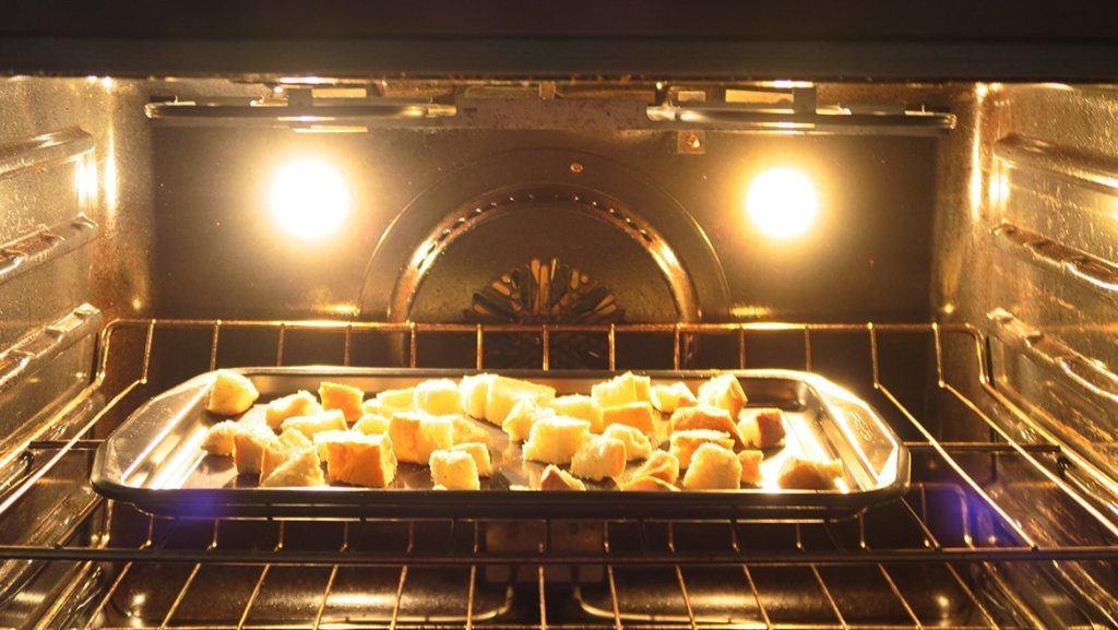Cubed bread on a baking sheet in the oven. Toasting the bread is the second step for making Tomato and Bread Salad.