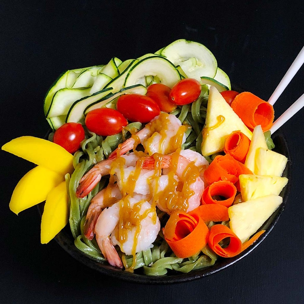 Top down view of Buddha Bowl with Pineapple Brown Butter Teriyaki Sauce with prawns, cherry tomatoes, mango, raw zucchini, carrots, and pineapple.