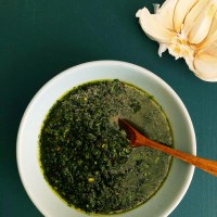 Topdown view of Garlicky Chimichurri in a blue bowl with fresh garlic in the background