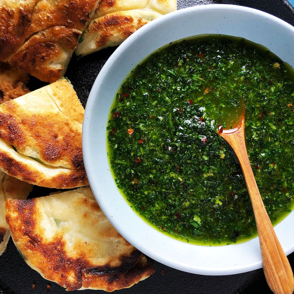 Topdown view of Garlicky Chimichurri , shown with green onion pancakes.