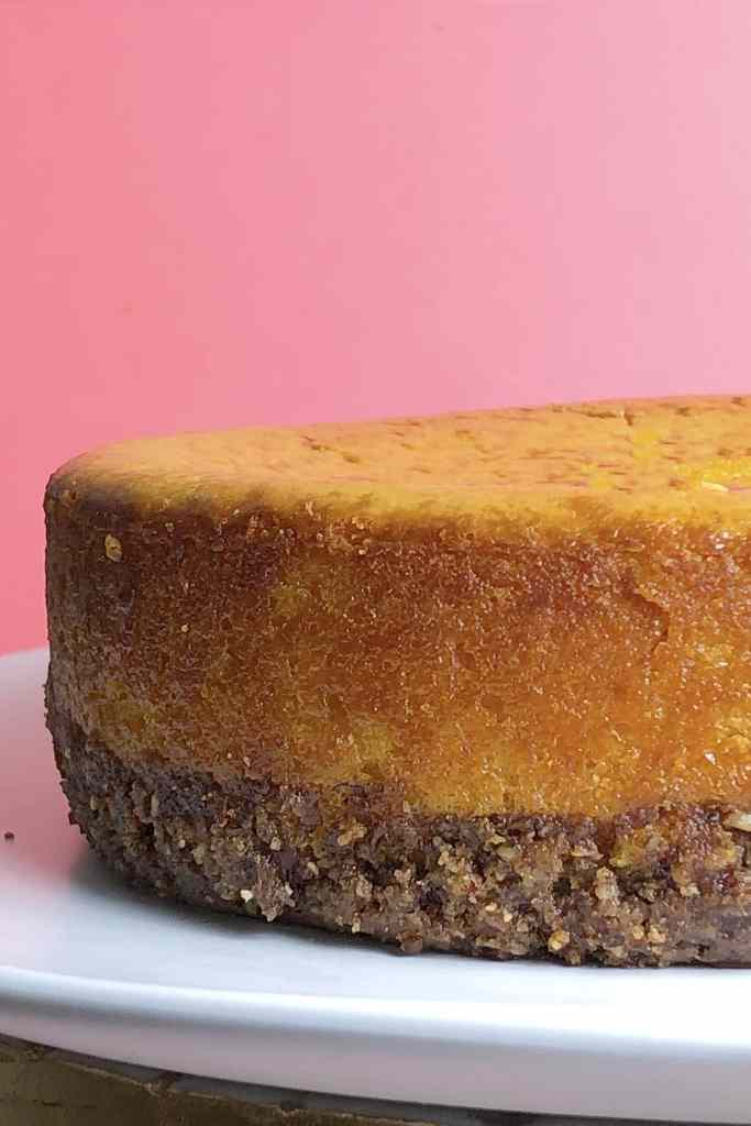Close up side view of Blood Orange and Carrot Cheesecake on a white plate, against a pink background