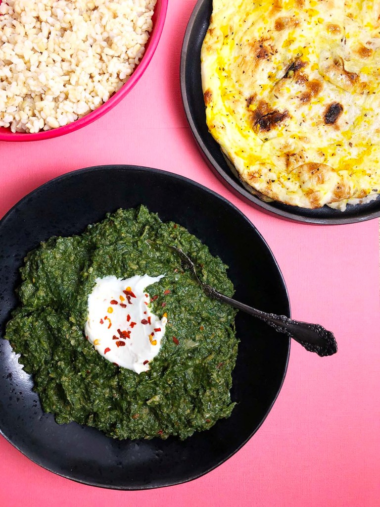 A top-down view of Indian-Spiced Spinach (also known as Saag). The Saag is in a black bowl, and it has a large dollop of yogurt as garnish, topped with red pepper flakes. The bowl is against a bright pink background. There is also a bright pink bowl with brown rice, and a black dish with garlic naan.