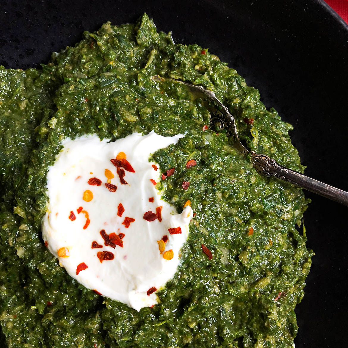 """A graphic titled """"Making Indian-Spiced Spinach (Saag): A Visual Guide. Displays the text """"Cook Spinach and set aside"""", next to an image of cooked spinach. Displays photograph of onions, ginger, and garlic in a frying pan, with text: Fry onions, ginger, and garlic. An image of the frying pan with a heap of dry spices on top of the previous ingredients. Text reads: Add spices and fry for 15 familycuisine.netlays photograph of yogurt and spinach on top of other ingredients in frying pan. Text reads: Add spinach and yogurt and heat through. Final image shows an immersion blender in the spinach. Text reads: Blend until desired consistency."""