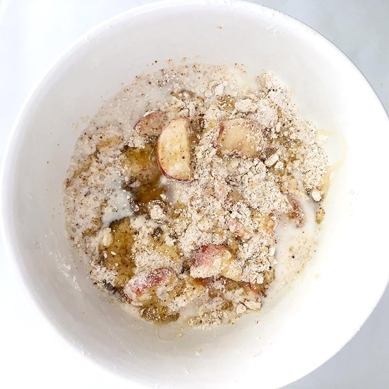 Top down view of milk and honey added to donut peach scone mixture, in white bowl