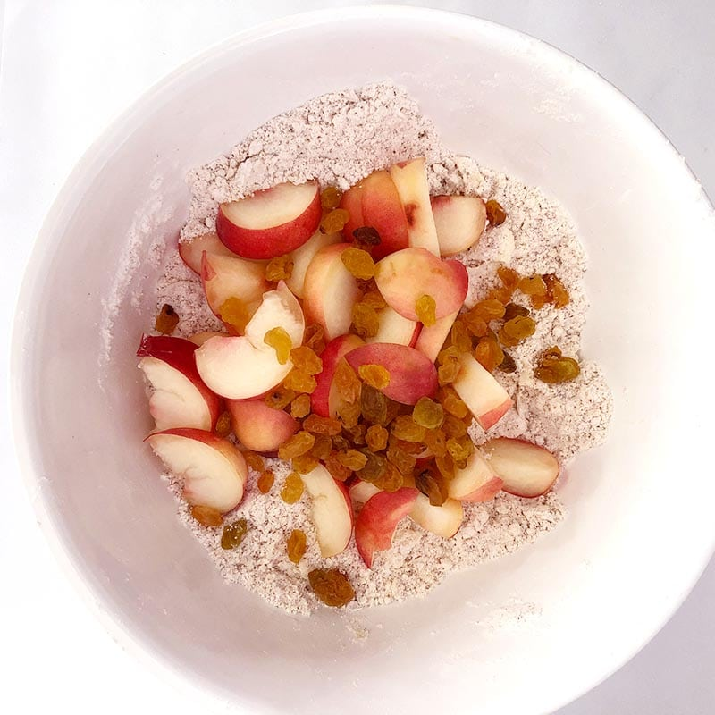 Top-down view of donut peaches and raisins added to crumbly mixture.