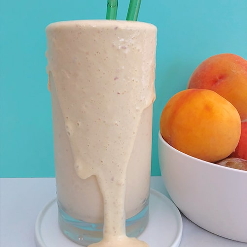 Double Peach Milkshake showing side view of peach milkshake pouring over the edge of a tall glass, with a bowl of peaches next to it.