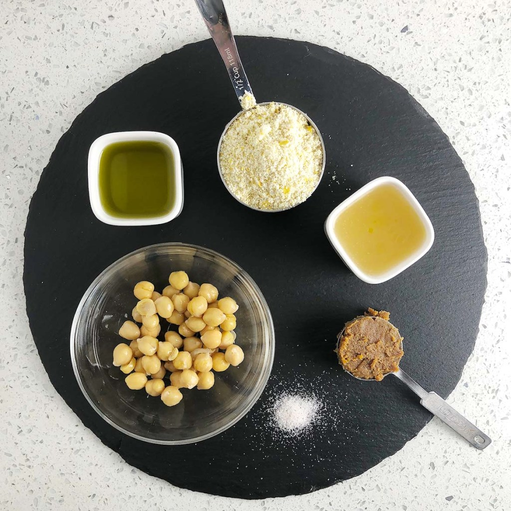 Top-down view of ingredients for Savoury Vegan Cheesecake: olive oil, Mother Mix (almond flour, nutritional yeast, tapioca starch, salt), aquafaba (chickpea liquid), miso paste, salt, and chickpeas.