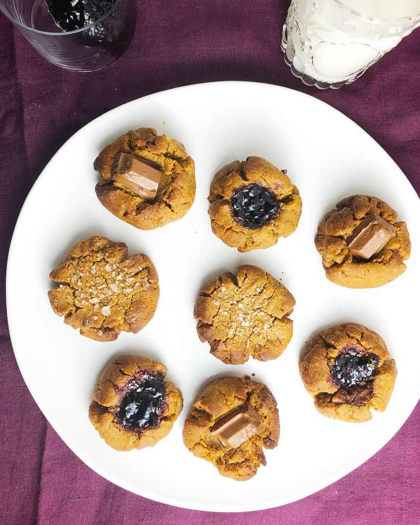 Top-down view of 1-Bowl Vegan Gluten-Free Peanut Butter Cookies on a white plate. Cookie versions include thumbprint style with jam and chocolate.