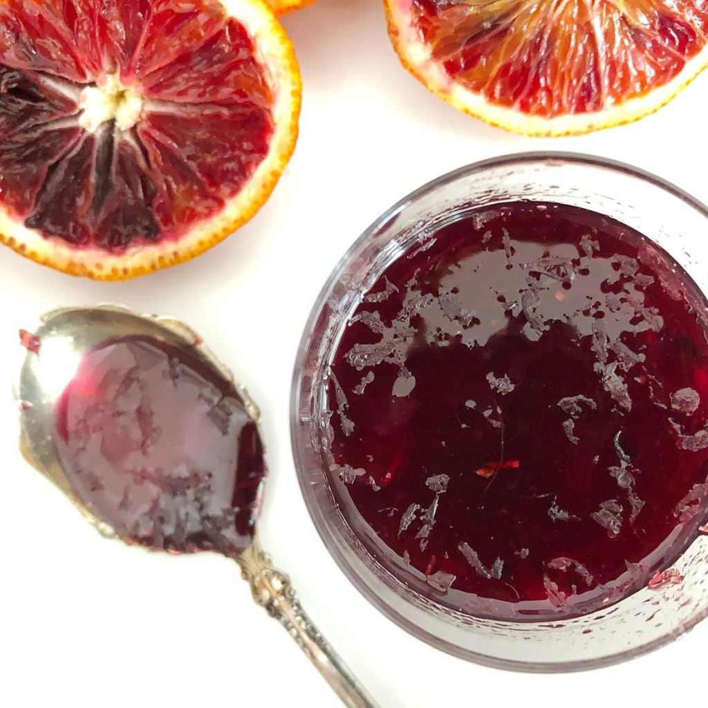 Top-down view of blood orange syrup in a glass jar, with blood oranges on a white plate.