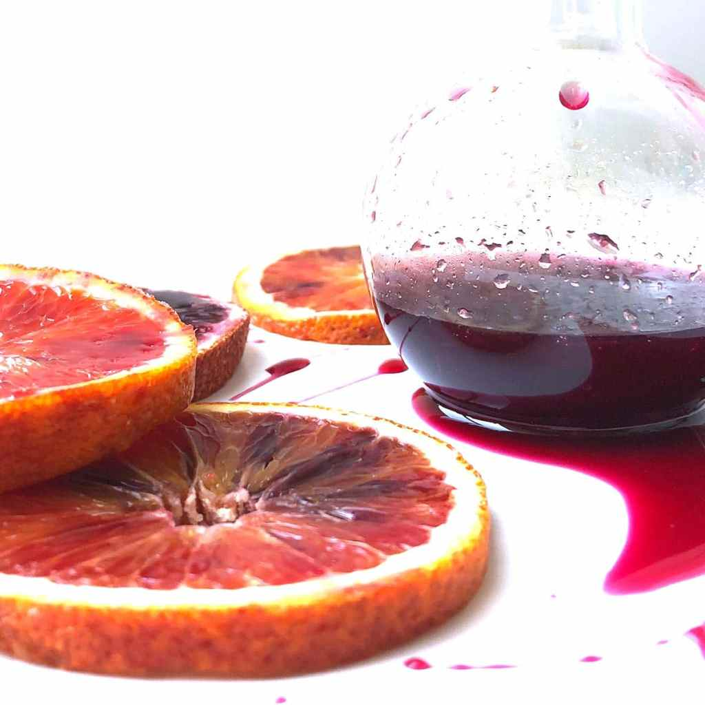 Side view of Blood Orange Syrup in a round jar, with blood orange slides, on a white plate