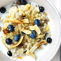 Top-down view of 1-Pot Barley Porridge topped with toasted coconut and blueberries.
