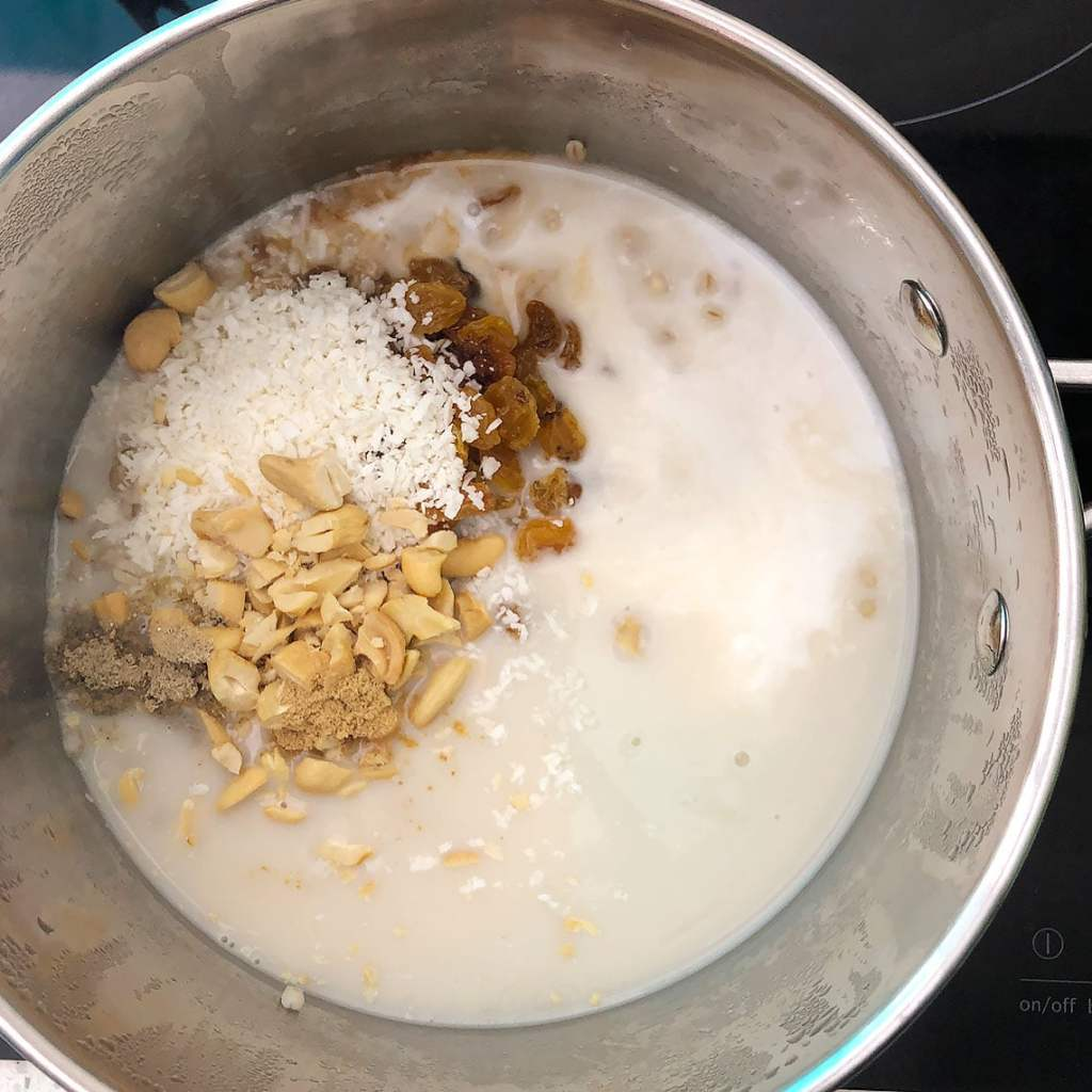 Top-down view of ingredients added to the cooked barley. These are cashew milk, coconut milk, chopped cashews, shredded coconut, raisins, vanilla, ginger, and cardamom. This is step 2 for making 1-Pot Barley Porridge.