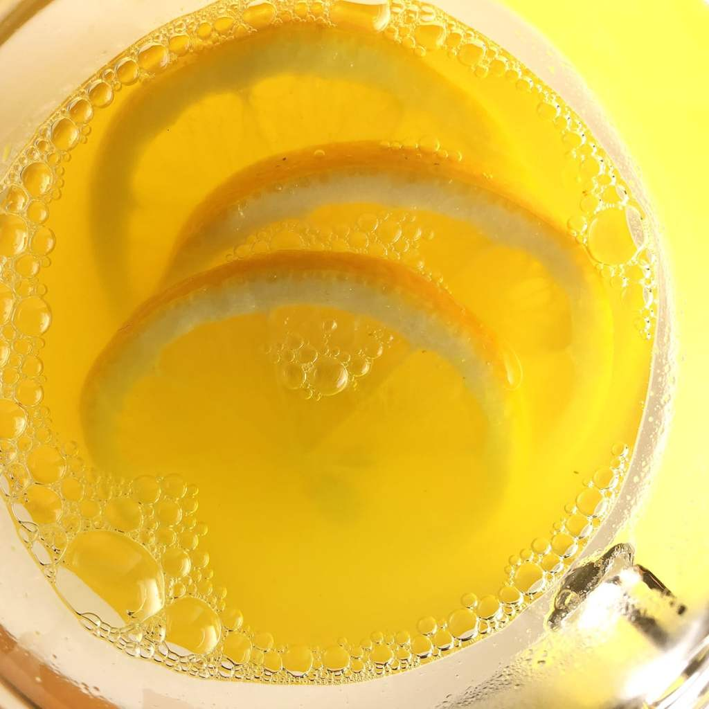 Top-down close up photo of hot lemonade bubbling in a clear glass. There are 3 lemon slices in the glass. The glass is set against a bright yellow background.