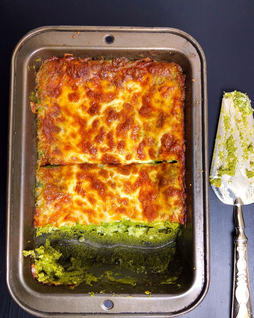 Top-down shot of green lasagna in a baking dish, with a slice of lasagna removed from the dish.