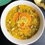 Top-down close up image of white bowl of lentil soup. Soup is garnished with pistachios, orange slices, and leek slices.