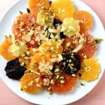 Top down shot of Simple Citrus Salad – slices of pink grapefruit, navel oranges, tangelos, blood oranges, and lemon, garnished with ribbons of toasted coconut, crushed pistachios and honey.