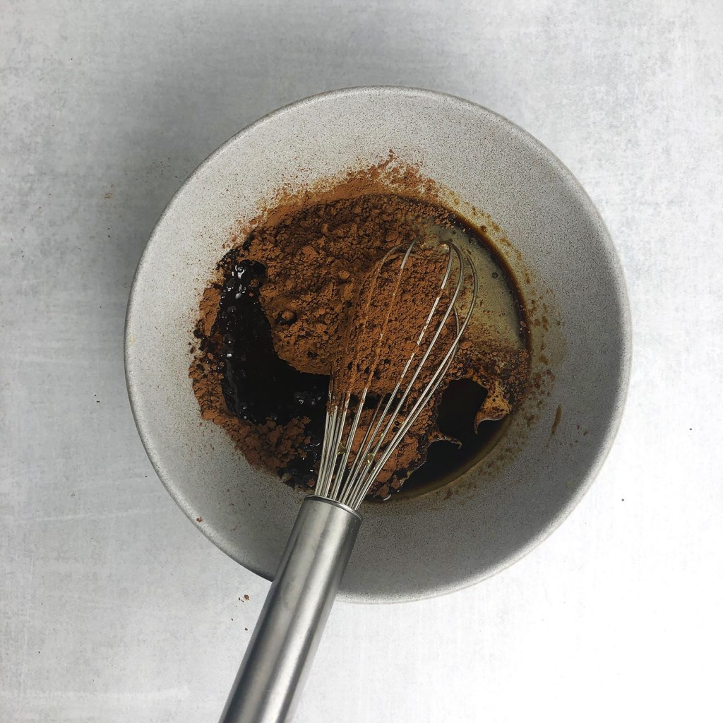 Top down shot of grey bowl with whisk. Bowl contains cocoa powder, espresso, brown butter, and coconut sugar.