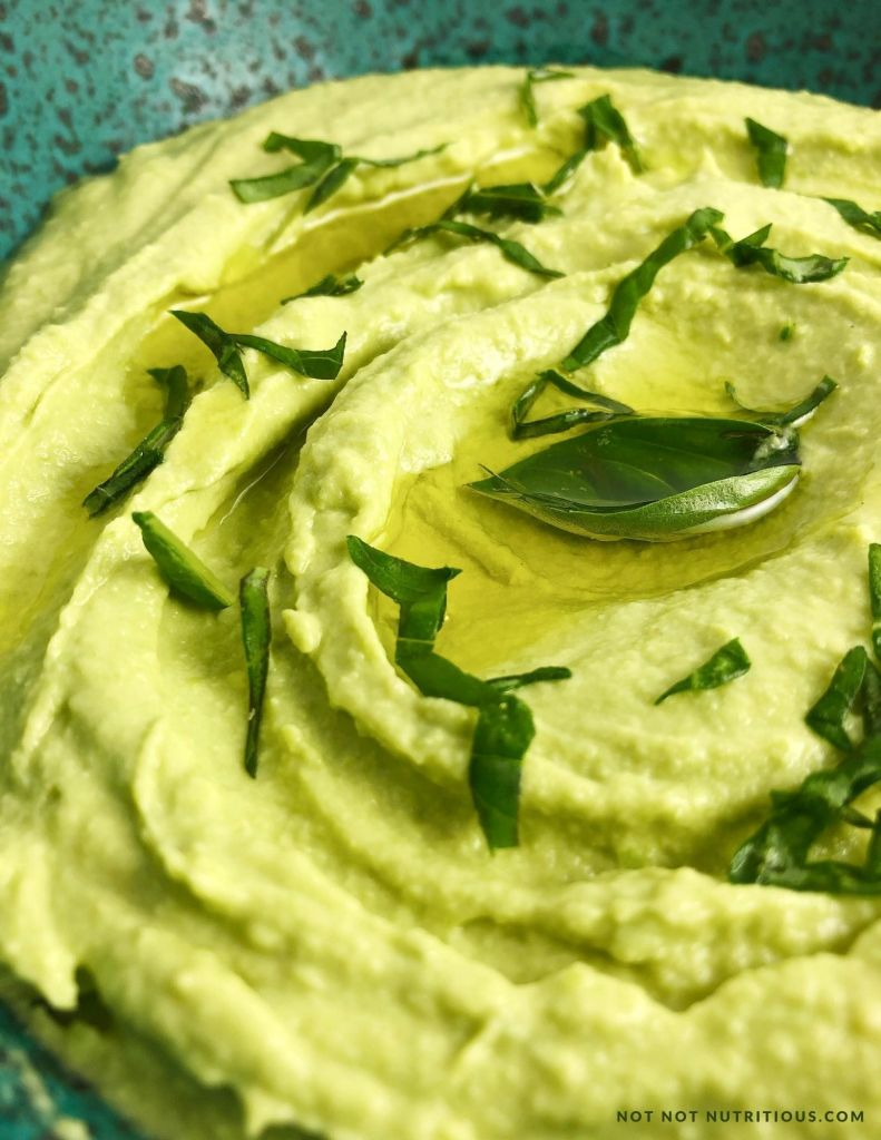 Top-down view of Basil Edamame Close up view of hummus in a blue speckled bowl. Hummus is pale green thanks to the basil and edamame beans. Hummus is topped with a bit of olive oil and fresh basil leaves.